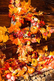Still life consisting of wicker wreath, orange leaves, autumn be Royalty Free Stock Photo