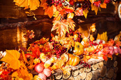 Still life consisting of wicker wreath, orange leaves, autumn be Royalty Free Stock Image