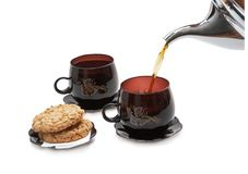 Still life - cookies, two cups and pouring tea. Royalty Free Stock Photos