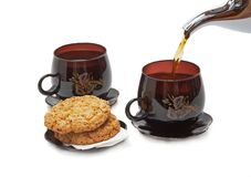 Still life - cookies, two cups and pouring tea. Royalty Free Stock Images