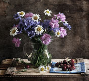 Still life with corn-flowers, camomiles and carnat. The bouquet of flowers consists of corn-flowers, camomiles, carnations Stock Photo