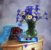 Still life with corn-flowers and merry. Bouquet of corn-flowers and camomiles in a glass vase on a stand, alongside dish with a merry Royalty Free Stock Images