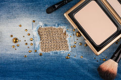 Still life from cosmetics on ragged jeans with rhinestones Royalty Free Stock Photos