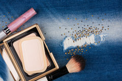 Still life from cosmetics on ragged jeans with rhinestones Royalty Free Stock Photography