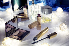 Still life: cosmetics on the table. Eyeshadow, mascara, lipstick and perfumes on the table Stock Photos