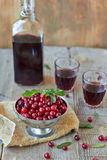 Still life. Cranberries and  red wine glasses and Bottle on a wooden background Royalty Free Stock Photos