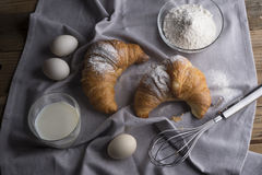 Still life of croissants, eggs, milk and flour. Stock Images