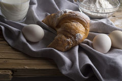 Still life of croissants, eggs, milk and flour. Royalty Free Stock Photo
