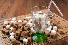 Still life of cubes of white and brown sugar in a glass and on a Royalty Free Stock Photo