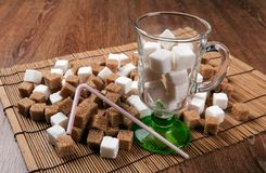 Still life of cubes of white and brown sugar in a glass and on a Stock Image