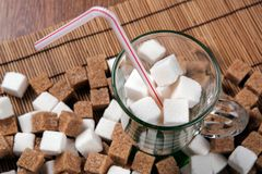 Still life of cubes of white and brown sugar in a glass and on a Stock Images