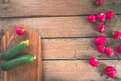 Still life of a cucumber radish on a wooden background. Still life of a cucumber radish on a wooden background Royalty Free Stock Images