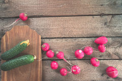 Still life of a cucumber radish on a wooden background. Still life of a cucumber radish on a wooden background Stock Image