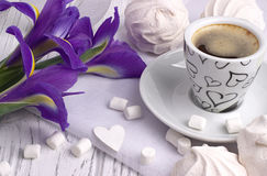 Still life with cup of coffe marshmallow zephyr iris flowers heart sign on white wooden background. Royalty Free Stock Photo