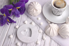 Still life with cup of coffe marshmallow zephyr iris flowers heart sign on white wooden background. Stock Photo