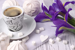 Still life with cup of coffe marshmallow zephyr iris flowers heart sign on white wooden background. Wedding. Valentines Day. Woman. S Day. 8 march Stock Photo