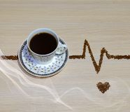 Cup of coffee. Still-life of a cup of coffee on the background with the line of the cardiogram of coffee grain Stock Photography