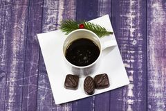 Still-life.a Cup of coffee on a beautiful plate, candy on a dark tree background stock image