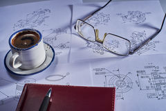 Still life with a cup of coffee, drawings of various designs, glasses. Writing-book and pen royalty free stock image