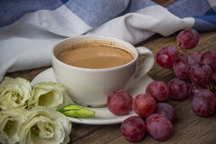 Still life with cup of coffee and flowers Eustoma and red grapes Royalty Free Stock Photo