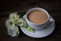 Still life with cup of coffee and flowers Eustoma on wooden back Stock Photo