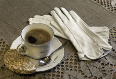 Still life with a Cup of coffee  and gloves. Still life with a Cup of coffee , biscuits and gloves Royalty Free Stock Photos