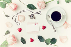 Still life - cup of coffee, peach roses, blank card, owl shaped clock, heart shaped candies on white background. Romantic still life - cup of coffee, peach roses Stock Image