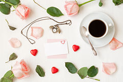 Still life - cup of coffee, peach roses, blank card, owl shaped clock, heart shaped candies on white background. Romantic still life - cup of coffee, peach roses Royalty Free Stock Photos