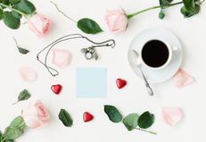 Still life - cup of coffee, peach roses, blue sheet of note, owl shaped clock, heart shaped candies on white background. Romantic still life - cup of coffee Royalty Free Stock Photography