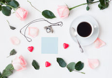 Still life - cup of coffee, peach roses, blue sheet of note, owl shaped clock, heart shaped candies on white background. Romantic still life - cup of coffee Stock Photo