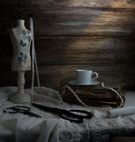Still-life with a cup of coffee, scissors, mannequin sewing and lace on a background of rough wooden walls. vintage.  stock image