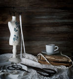 Still-life with a cup of coffee, scissors, mannequin sewing and lace on a background of rough wooden walls. vintage.  stock photography