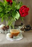 Still-life with a cup of coffee, sweets and peonies Royalty Free Stock Photography