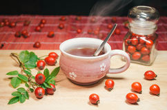 Still life with cup of fresh tea and rose hips on the wooden table Stock Photos