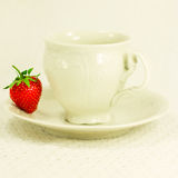 Still-life with cup, saucer and strawberry. Still-life with white elegant single tea set and strawberry on a white inwrought fabric background Royalty Free Stock Images