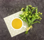 Still life with cup of tea and flower bouquet. Flat lay royalty free stock photo