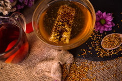 Still life of cup of tea, honey, honeycombs, wax and pollen gran Royalty Free Stock Photos