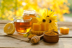 Still life from cup of tea , lemon, honey, wax. Honeycombs and pollen granule on wooden table Royalty Free Stock Photos