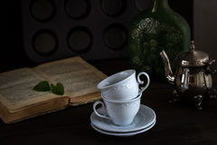 Still life with cups and book in vintage style Royalty Free Stock Photo