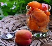 Still life with cut apricots in a glass, one whole fruit, spoon placed on straw plate. Stock Photos