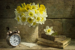 Still life with daffodils. Old books and clock on wood background Royalty Free Stock Photo