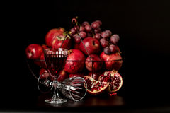 Still life on a dark background. Wine (liquor) glasses, fruits a Stock Photography