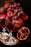 Still life on a dark background. Wine (liquor) glasses, fruits a Royalty Free Stock Images