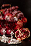 Still life on a dark background. Wine (liquor) glasses, fruits a Royalty Free Stock Image