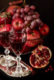 Still life on a dark background. Wine (liquor) glasses, fruits a Stock Image