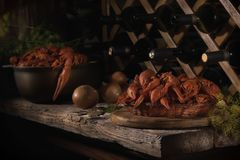 Still life in dark colors in wine cellar with red crayfish. stock photo