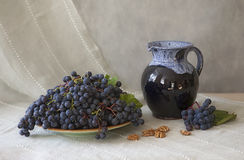 Still life with a dark grapes and blue jug. On the background of the drapery Royalty Free Stock Photography