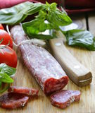 Still life of delicacy salami, tomatoes and basil Stock Images
