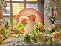 Still life with delicate yellow roses, glass candlesticks, an old upstanding plate with pink flower border. In front of it a matching water carafe in Art stock photography