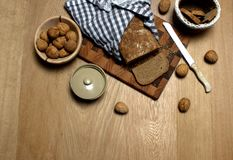 Still life of a delicious home made bread with some walnuts on the side. Butter cup, cutting board Stock Photos